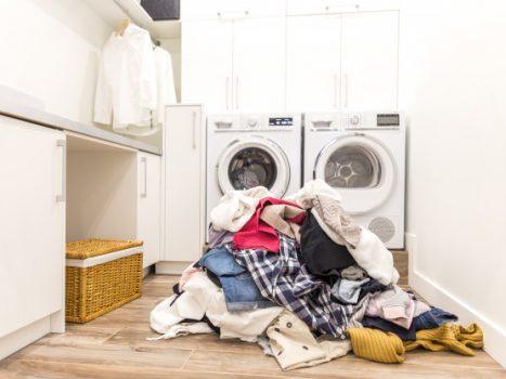 En bunke vasketøj ligger ved en vaskemaskine og tørretumbler
