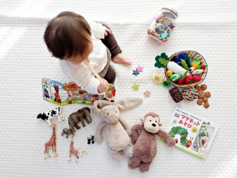 Baby der sidder på et tæppe med legetøj